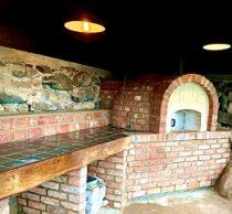 Vedfyrt pizzaovn montert på kjøkkenbenk